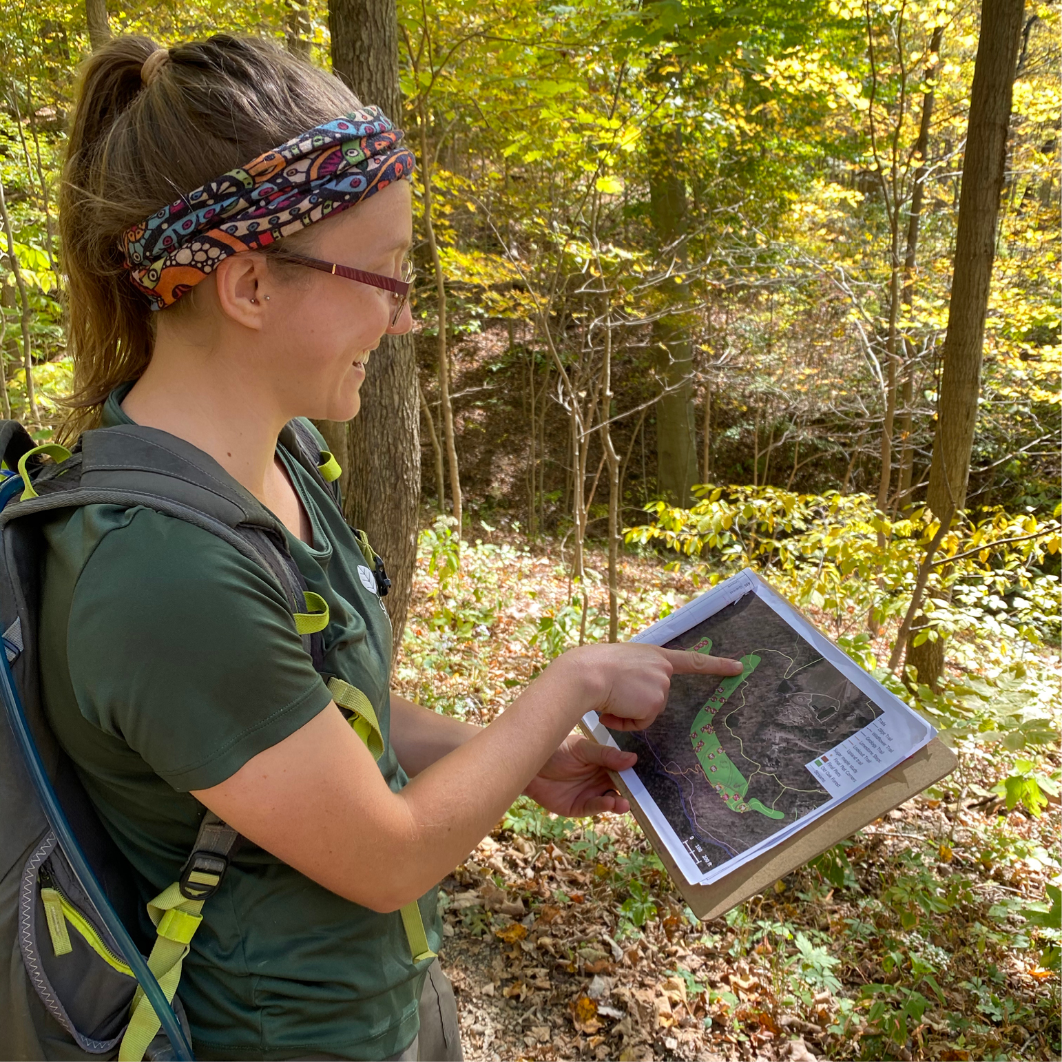 Danie Frevola, a young white woman, points to a map in a forest as she conducts her research at Rowe Woods