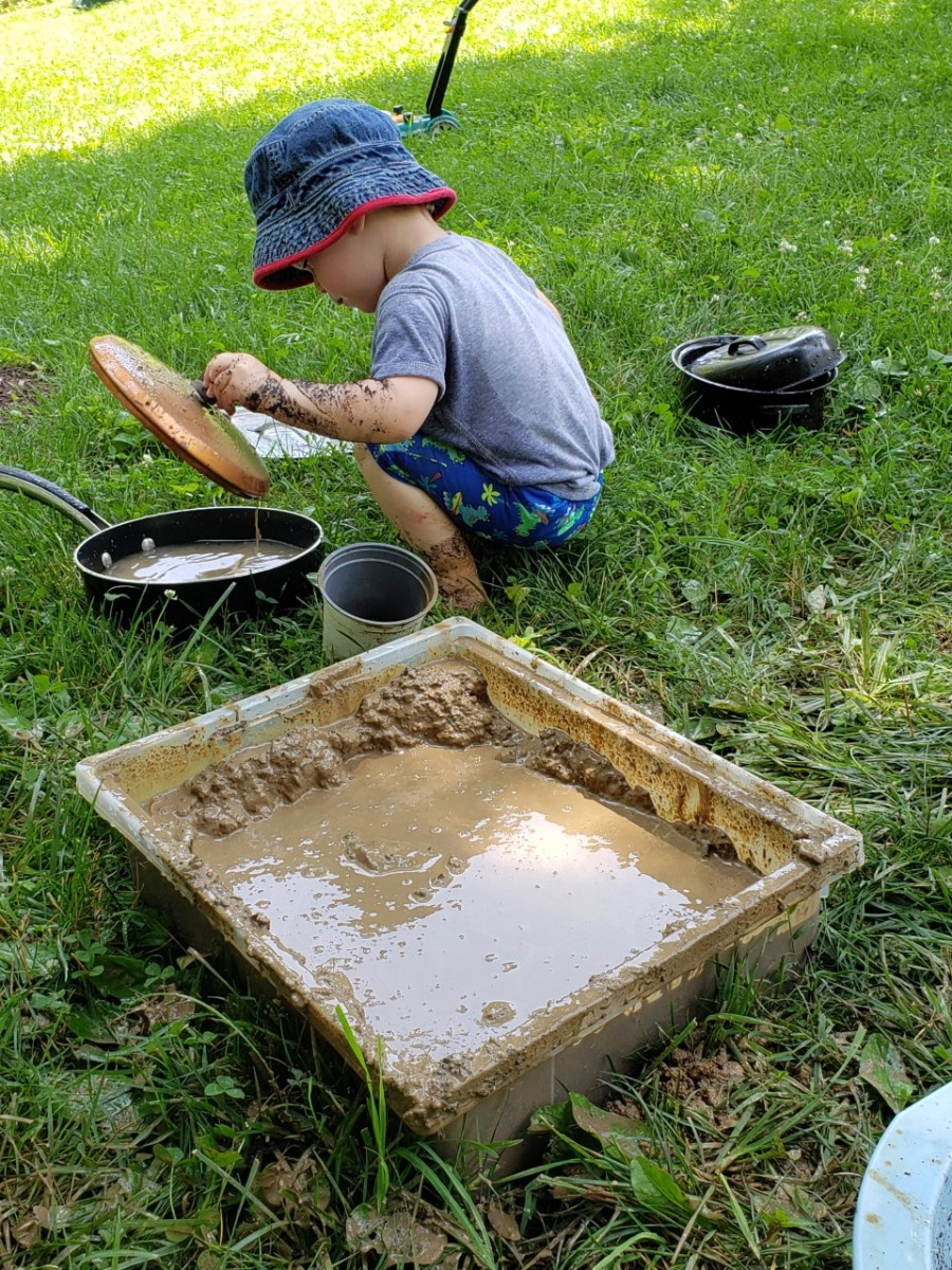young boy pretend cooking with mud