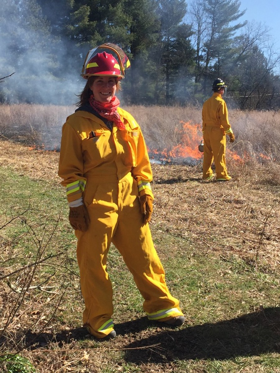 Olivia smilling for a photo as another individual completes a controlled burn in the background