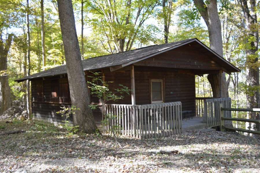 cabin with wooden front porch in the woods