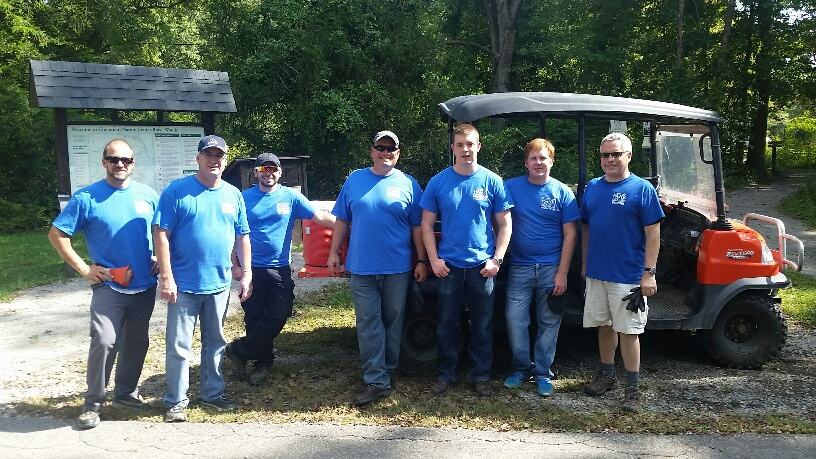 Seven people in blue shirts standing in front of a red golf cart